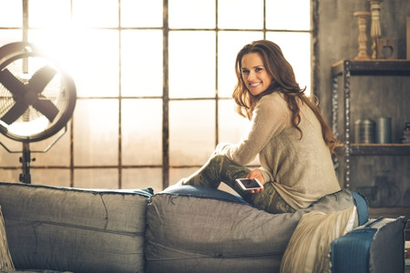 chic woman: A brunette woman is smiling with phone sitting on the back of a sofa. Industrial chic ambiance and cozy atmosphere, sunlight is streaming through the loft window. Stock Photo