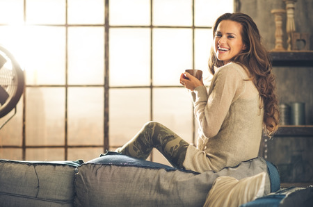 comfortable: A brunette long-haired woman is seen from the side while sitting on the back of a sofa. She  is smiling and holding a hot cup of coffee. Industrial chic background, and cozy atmosphere. Stock Photo