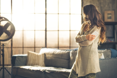 A brunette woman in comfortable clothing is standing in a loft living room, holding her phone, arms crossed, looking away. Urban chic loft decoration details and window.