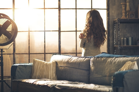 Looking away, a brunette woman in comfortable clothing is standing in a loft living room, hugging herself, looking out the window. Urban chic loft decoration details and window.