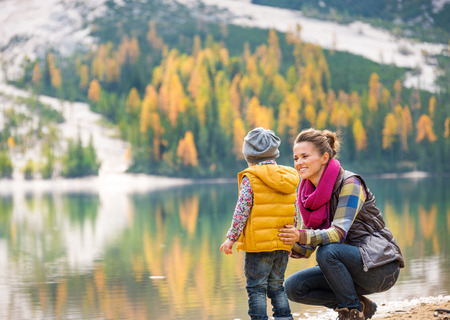 With a background of autumn colours and leaves, a mother in hiking gear is kneeling next to her daughter. The daughter is seen from behind and looking out at the lake.