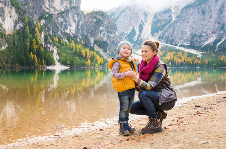 Against a background of autumn colours and leaves, a mother in hiking gear is kneeling and smiling next to her daughter. The mountains and trees are reflected in the lake.