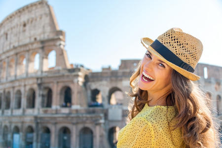 A woman is turning and looking over her shoulder while laughing, enjoying being a tourist in the beautiful city of Rome. In the background, the Colosseum.