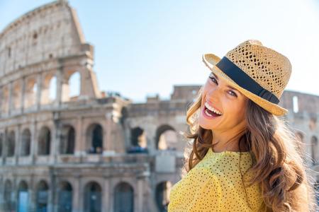 riendo: Una mujer está girando y mirando sobre su hombro mientras riendo, disfrutando de ser un turista en la hermosa ciudad de Roma. En el fondo, el Coliseo.