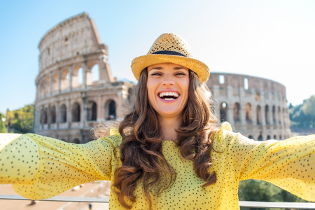 A happy, smiling woman tourist in the summer takes a selfie with the Colosseum in the distance. Archivio Fotografico