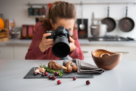 cameras: A woman food photographer in the background leans down to take a close-up, in a modern kitchen, of autumn fruits and vegetables - mushrooms, garlic, rosemary, and cranberries.