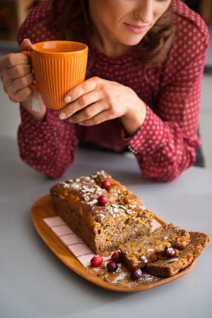 pumpkinseed: Ah, the sweet smells of autumn. An elegant woman is holding her cup of tea, leaning on a kitchen counter. In the foreground, a freshly-baked loaf of sliced pumpkin, cranberry, and pumpkin-seed bread.