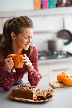calabaza: Una mujer est� sonriendo y relajante mientras ella se apoya en el mostrador de la cocina