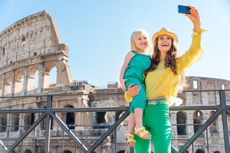 A brunette mother wearing a hat in the summer in Rome is holding her blonde daughter. They are smiling and taking a selfie. In the distance, the Colosseum.