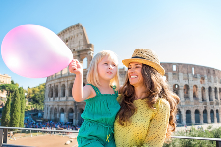 mam: A brunette mother wearing a hat in the summer in Rome is holding her blonde daughter, who is waving a pink balloon. In the distance, the Colosseum and summer tourists.