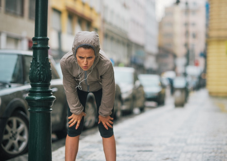 A woman jogger leans down to breathe deeply, taking a break and stretching. She is wearing rain gear for her workout.