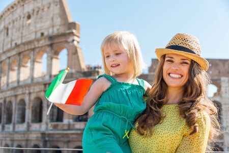 Portrait of a smiling brunette mother wearing a hat is holding her blonde daughter who is waving an Italian flag in the summer. In the distance, the Colosseum.