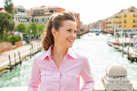 A pretty brunette tourist leans casually against a bridge over one of Venices canals, smiling and looking into the distance. Stock Photo