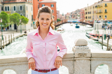 An elegant brunette tourist leans casually against a bridge over one of Venices canals, smiling.  Stock Photo