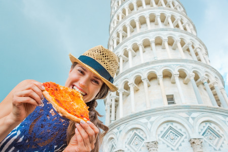 eating pizza: Delicious! A bite of fresh Italian pizza while standing in front of the Leaning Tower of Pisa - what an experience...