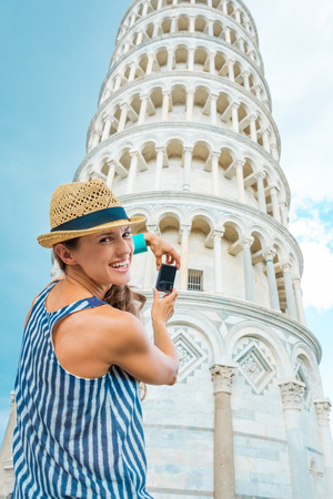 A happy brunette smiles over her shoulder, pausing from taking a photo on her digital camera of the Leaning Tower of Pisa.