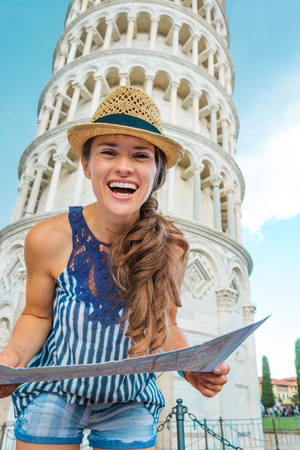 A happy woman tourist wearing a hat is holding a map and laughing. Behind her, the Leaning Tower of Pisa. Stock Photo