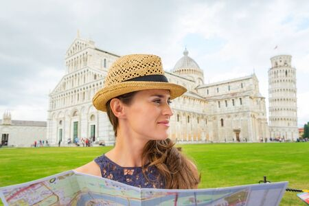 A woman wearing a straw hat smiles gently as she holds a map.