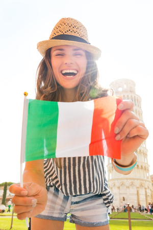 A happy woman tourist is proudly holding an Italian flag while leaning down and laughing.