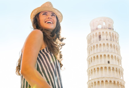 A happy female tourist is smiling, looking back over her shoulder. In the distance, the Leaning Tower of Pisa.