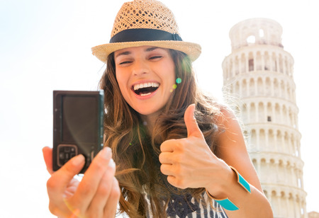 A smiling, laughing woman tourist is taking a selfie at the Leaning Tower of Pisa, giving a happy thumbs up. What a joy it is to travel!