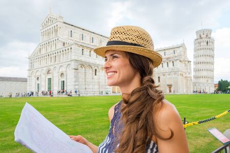 A smiling female tourist holding a map is looking into the distance. How beautiful Pisa is! Behind her, the Piazza dei Miracoli and the Leaning Tower of Pisa.
