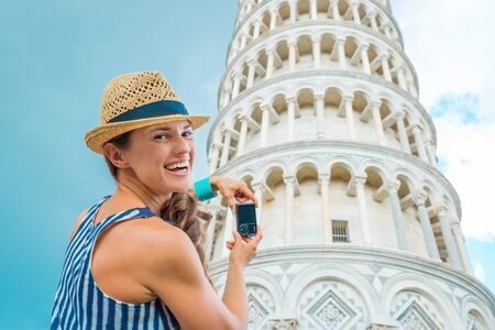 I bet I could take hundreds of photos of the Leaning Tower of Pisa and never get tired of it... A happy brunette smiles over her shoulder, pausing from taking a photo on her digital camera.
