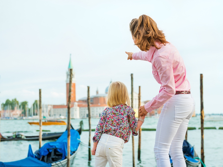 Look at the church, my sweet, says this mother, who is pointing out the sights to her daughter while holding her hand. Stock Photo