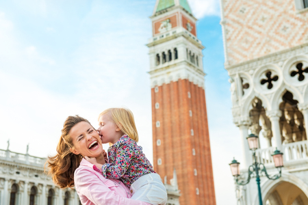 What makes Venice even more magical are kisses... Here, a little girl gives her mother a kiss on the cheek while her mother holds. The mother is laughing and delighted.