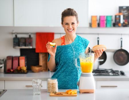 witaminy: A pasuje brunetka uśmiecha się radośnie, jak ona jest dodanie jabłko do jej świeżo wykonane smoothie