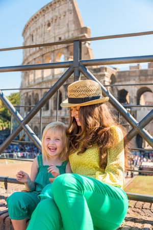 A brunette mother wearing a hat in the summer in Rome is sitting next to her blonde, smiling daughter. They are happy. In the distance, the Colosseum and summer tourists. Stock Photo