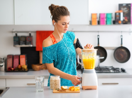 A sporty woman is standing in her kitchen, making a smoothie with fresh, seasonal fruits, nuts, and oats, to complete her healthy start to the morning.