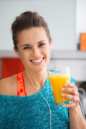 finished good: Cheers to you, and to your good health. A happy, sporty woman has just finished a good workout and is rounding it off with a freshly-made smoothie. Packing the vitamins in tastes so good...