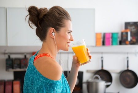 In her modern kitchen, a woman in profile is about to drink her freshly-made smoothie, which is packed with vitamins. A healthy lifestyle is so much fun. Foto de archivo