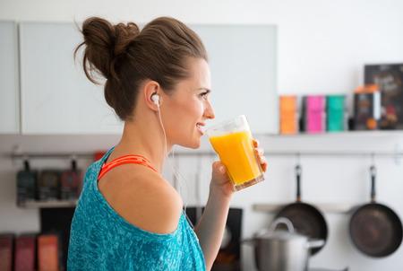 tomando jugo: En su cocina moderna, una mujer de perfil est� a punto de beber su batido reci�n hecho, que est� lleno de vitaminas. Un estilo de vida saludable es muy divertido. Foto de archivo