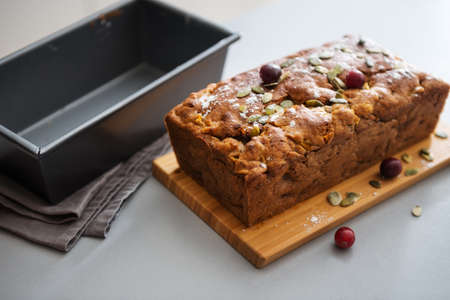 On a kitchen counter, a freshly-baked cranberry and pumpkin seed loaf is standing and cooling on a wooden cutting board.