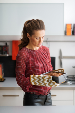 A woman is standing, looking down at the golden brown loaf of fruit and nut bread she has just taken out of the oven. Stock Photo