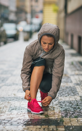 supposed: A pop of pink colour adds a bit of spring to my step... Or at least it is supposed to. A woman jogger wearing rain gear is kneeling down to tie her running shoe before continuing on her run.