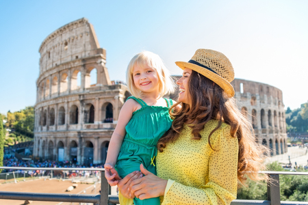 A brunette mother wearing a hat is holding her blonde, smiling daughter in her arms. In the distance, the Colosseum and summer tourists.