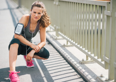 An athletic woman wearing earbuds and her device in a cuff on her arm is getting ready to go on a run. She is looking into the distance at the road ahead.