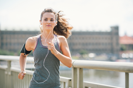 An athletic woman is jogging on a bridge, listening to music. Her long hair is up in a ponytail and blowing in the wind.