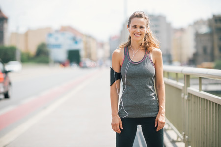A woman is smiling happily as she takes a break on a bridge. She is relaxed, happy, and fit, and enjoying the workout in the sunshine.