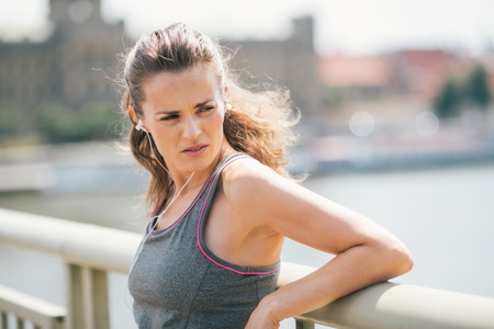 Closeup of a brunette jogger looking over her shoulder as she is resting on a bridge and looking over her shoulder while listening to music. Stock Photo