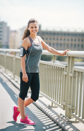 An athletic woman in pink sneakers stands on bridge, smiling and resting. It is summer time, she has just worked out, and is loving the beat of her music and the buzz of a good workout in the sun.