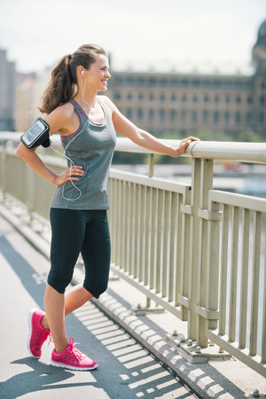 An athletic woman in pink sneakers stands on bridge, is relaxing, standing with a hand on her hip, while smiling and resting. Looking out at the city, she feels good.
