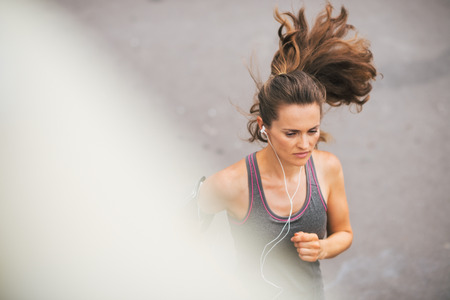 A woman jogger is running, concentrated and in the zone as she listens to music on her earbuds.