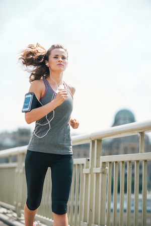 stride: Finding my stride to the beat of the drums... An athletic woman hits her stride as she jogs on a bridge above an urban river. She is concentrating and in the groove. Working out feels great. Stock Photo