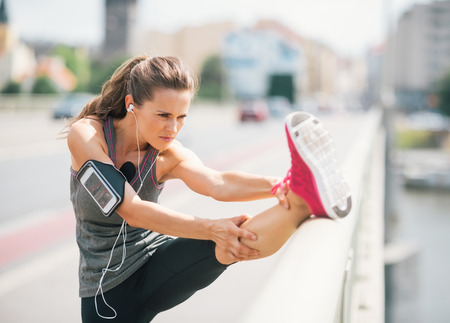 An athletic woman stretches out before going on a long run. She is wearing a cuff on her arm that is holding her device. On it, she is listening to some motivational music.
