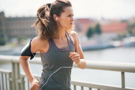 Rock on, draaien op, kracht door. Dat is het spul van de kampioenen. Een brunette, langharige jogger is diep in gedachten, gericht op haar doel en wordt gemotiveerd door haar de muziek die ze luistert naar. Stockfoto