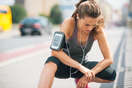 An athletic woman wearing earbuds and her device in a cuff on her arm is looking down at the ground, listening intently to the music. Stock Photo